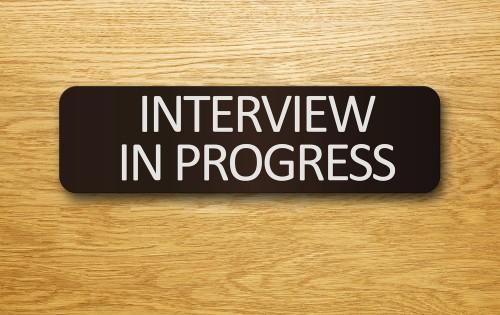 """""""Interview In Progress"""" sign on an office door."""