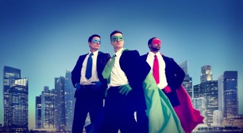 Three business leaders in superhero costumes in front of New York skyline