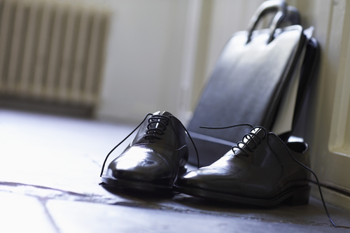 Dress Shoes and briefcase on floor close up.