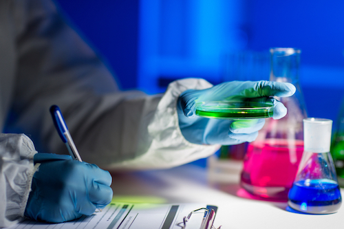 close up of scientist writing test results in lab