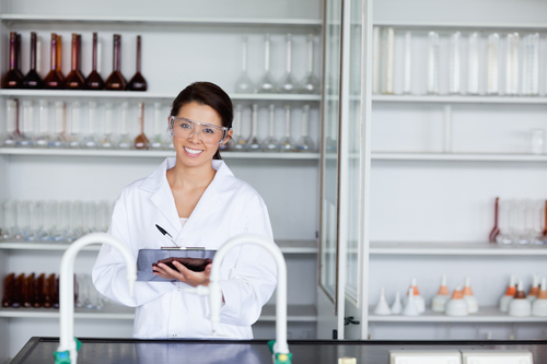 Smiling woman in laboratory writing on a clipboard.
