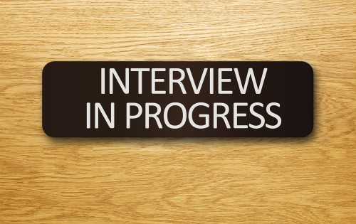 """Interview In Progress"" sign on an office door."