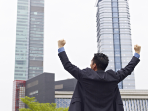 asian businessman celebrating with arms raised