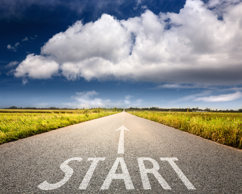 """An empty road that says """"START and an arrow pointing forward."""