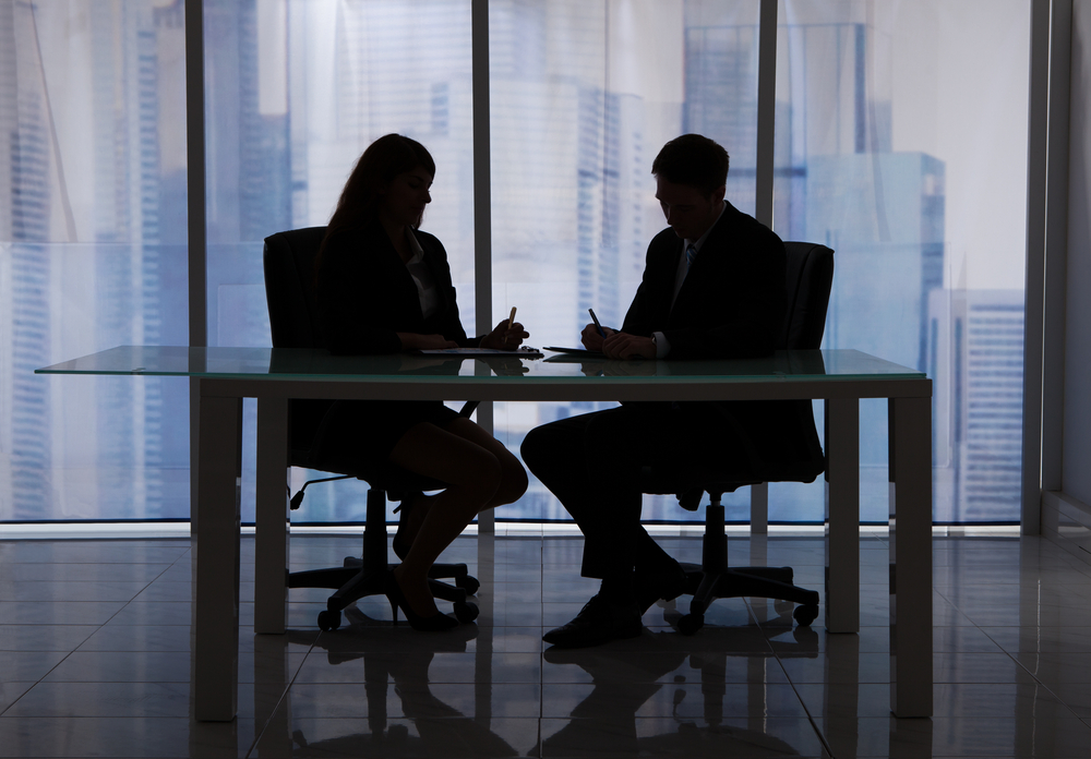 Silhouette of businessman and businesswoman working privately in an office