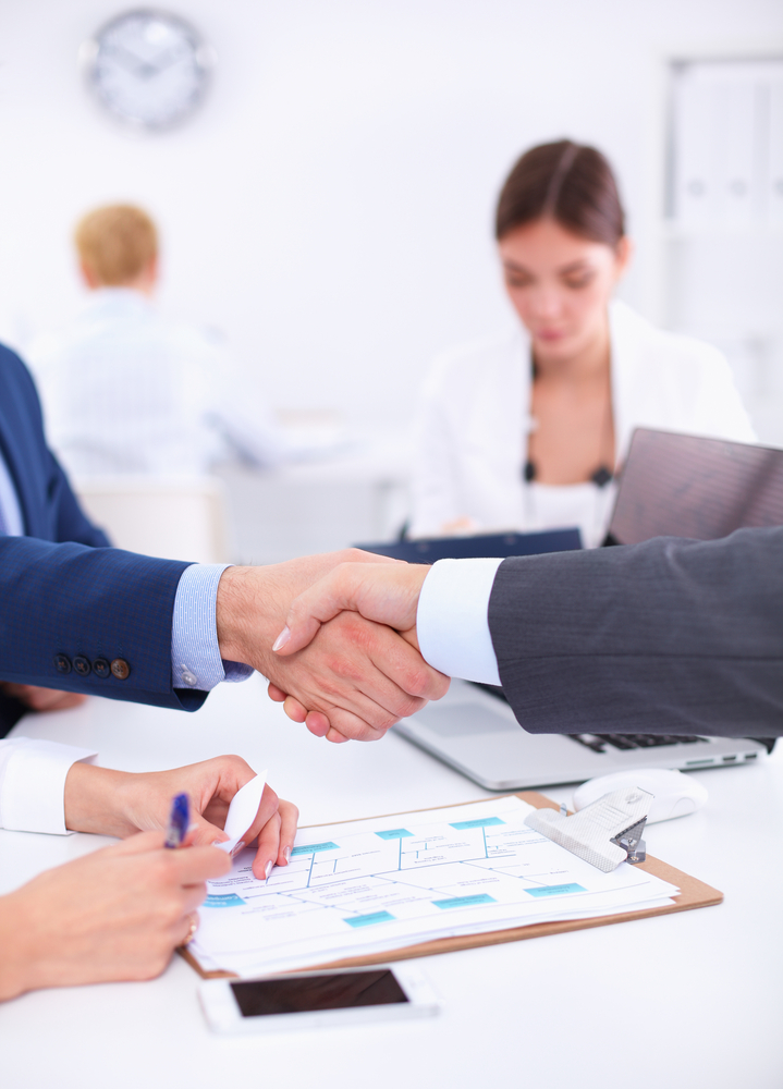 Business people shaking hands, finishing up a meeting, in medical office.