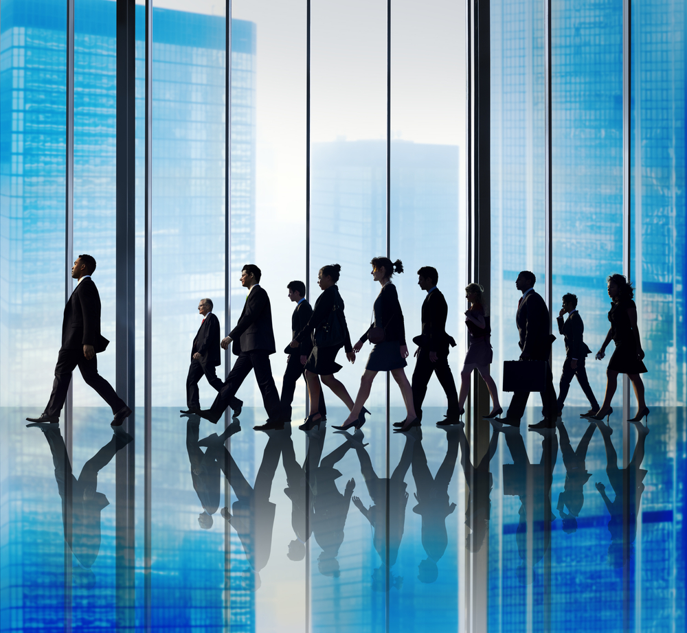 Business people follow leader in corporate office hallway