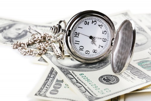 Silver pocket watch lies open on $100 bills close-up. Time is money concept.
