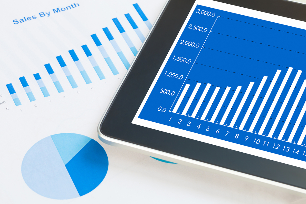 digital tablet and smartphone with financial chart report, paper, pen on work table