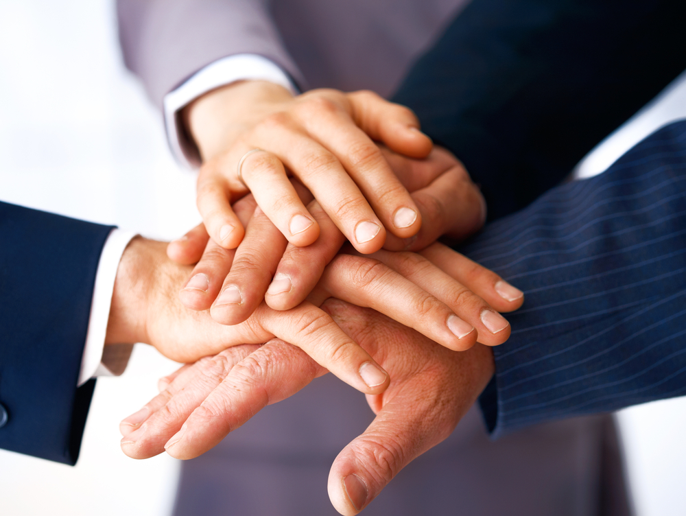 Close-up of business people's hands stacked on top of one another - teamwork concept