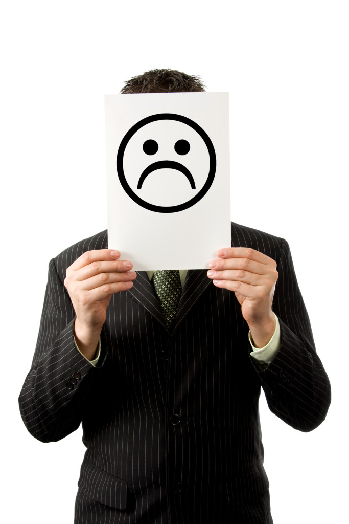 Businessman holding up a sad smilie picture in front of his face.