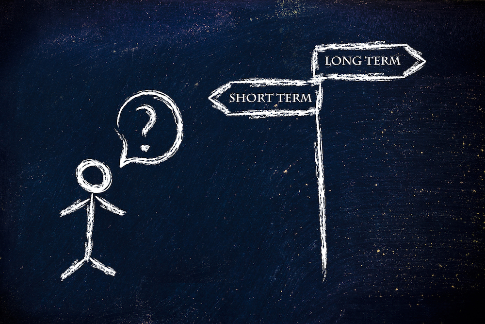 Design on blackboard depicting business choices: short or long term, which is the priority?