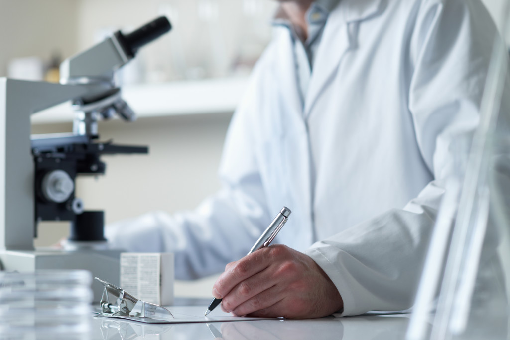 Clinical worker taking notes by a microscope in the lab.