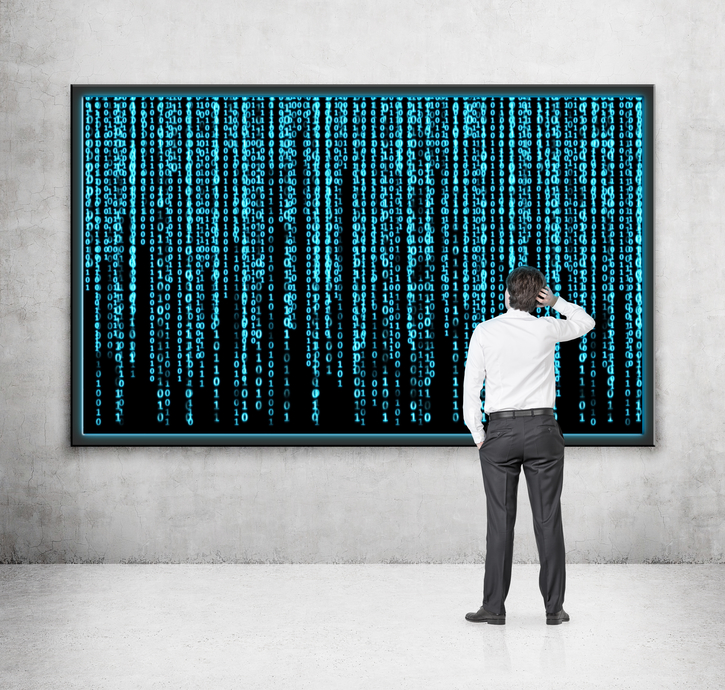 Businessman looking at a screen filled with a matrix of numbers and scratching his head.