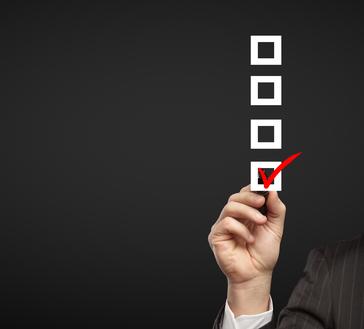 a hand checks off a box on a checklist