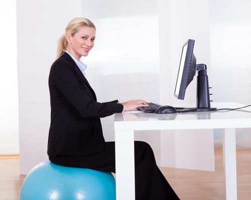 An elegant young blonde works at her office desk while sitting on a pilates ball.
