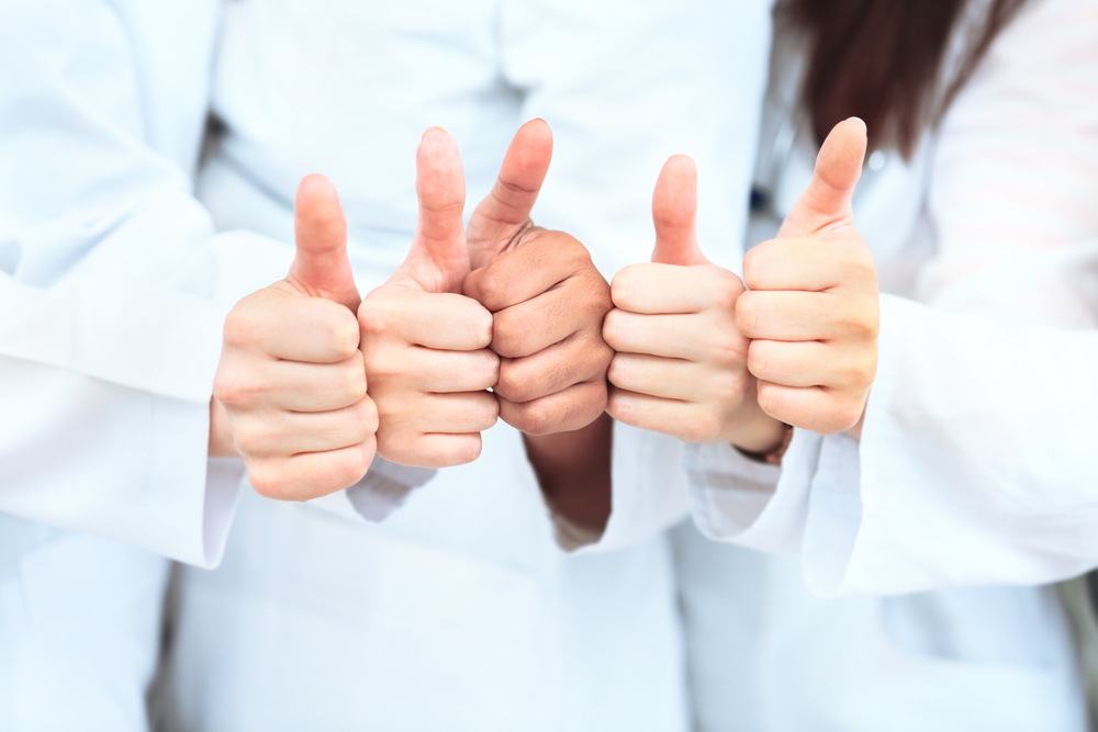 Portrait of confident doctors team showing thumbs up.