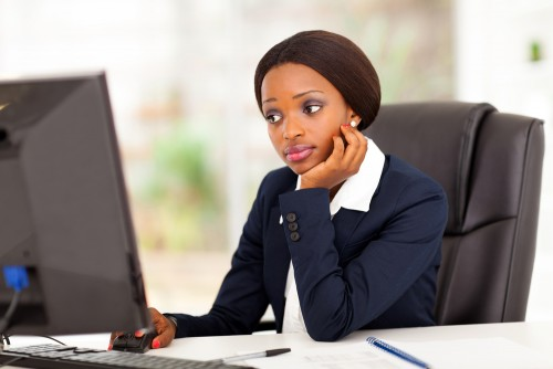 Thoughtful businesswoman looking at computer screen in office.
