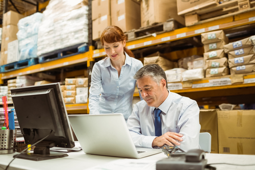 Warehouse management talking and looking at laptop.