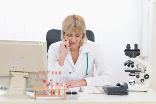 Concentrated female doctor working at office.