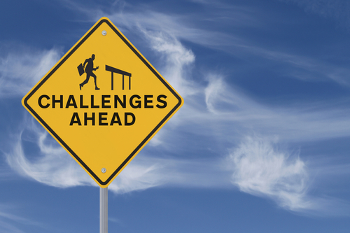"Road sign that says ""Challenges Ahead"" and shows the silhouette of a businessman about to jump over a hurdle."
