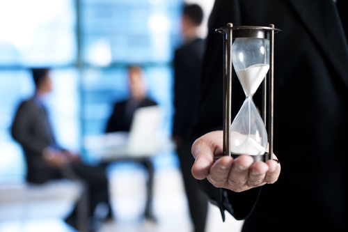 Make the most of your meeting time. Businessman holding an hour glass during a meeting.